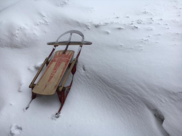 vintage red wood and metal sled in snow bank